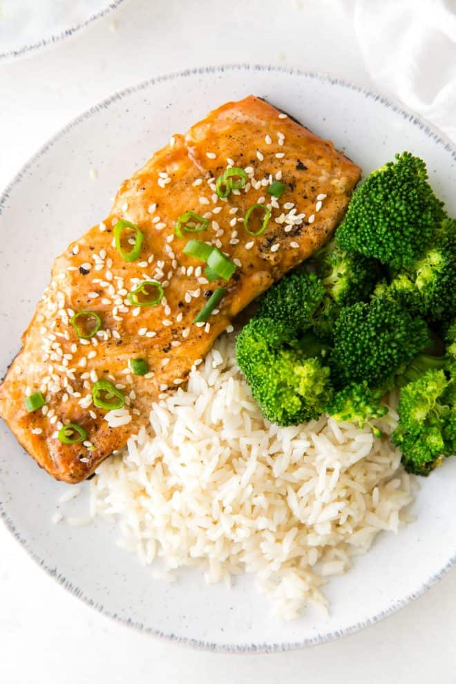 A plate with teriyaki glazed salmon fillet topped with green onions and sesame seeds, broccoli and rice.