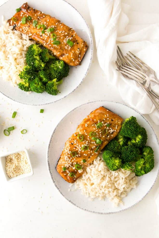 Two plates with teriyaki glazed salmon fillet topped with green onions and sesame seeds, broccoli and rice on a table, with 3 forks and a bowl of sesame seeds.