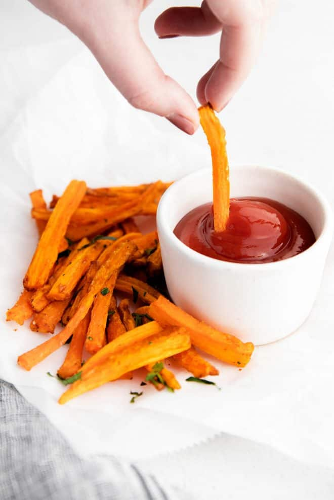 dipping a carrot fry into ketchup