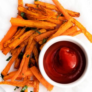 air fryer carrots sitting on a plate with a side of ketchup