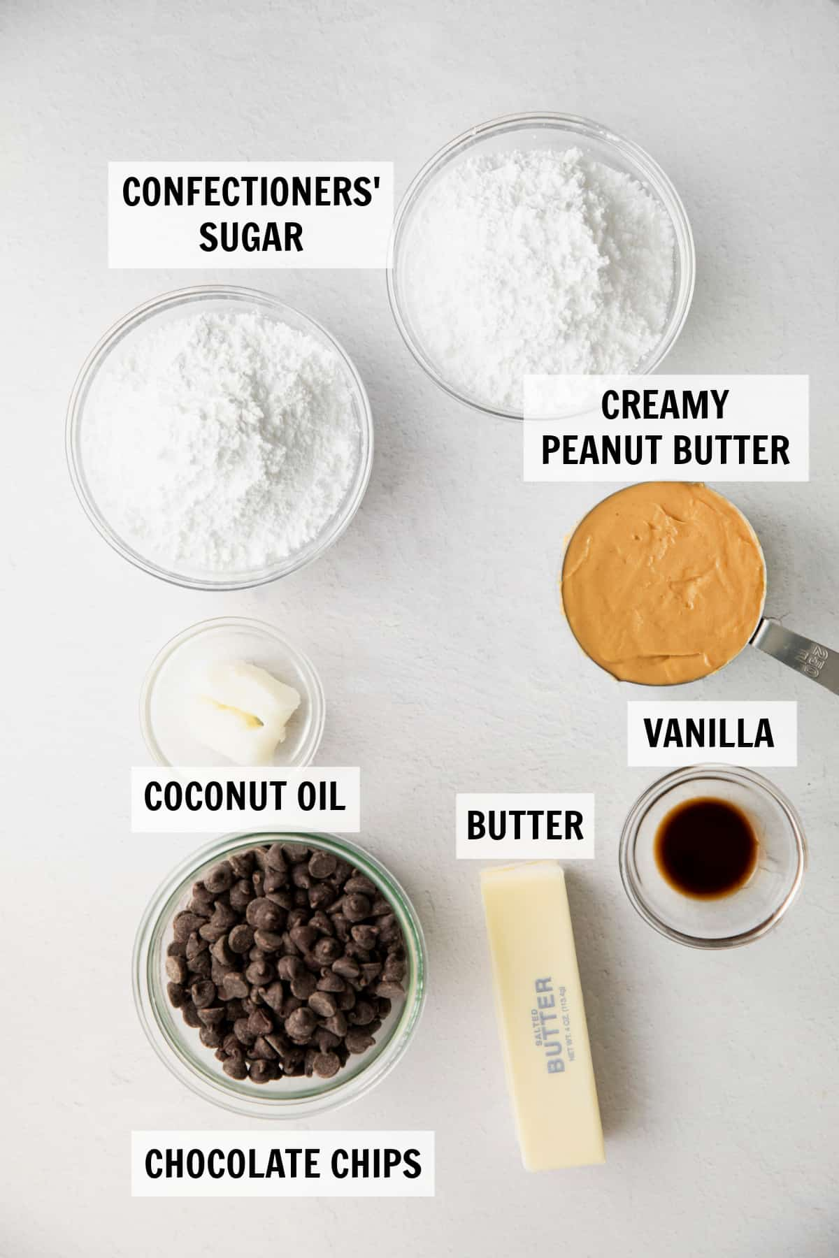 ingredients for buckeye bars in bowls on a white tabletop