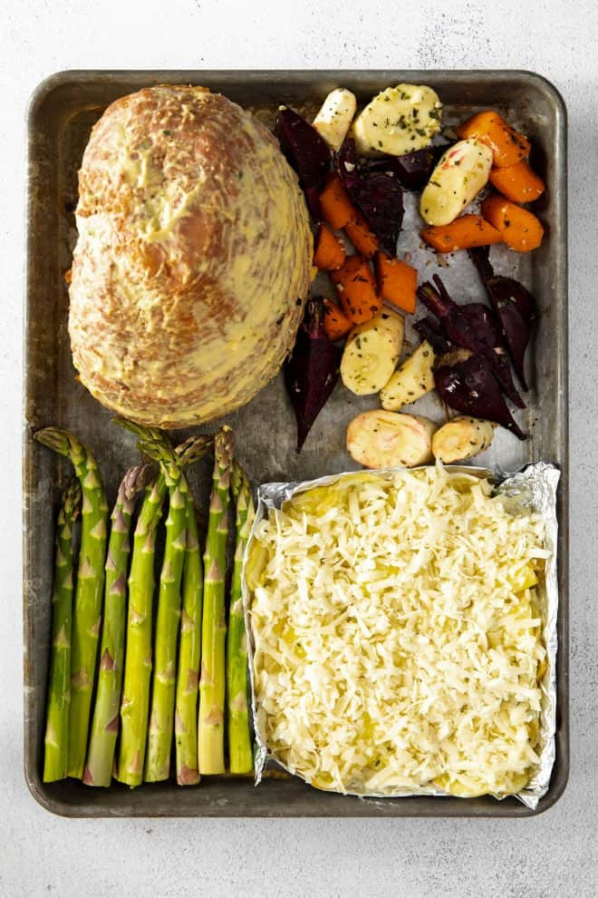 ham, root vegetables, asparagus and potatoes on a sheet pan before baking in the oven