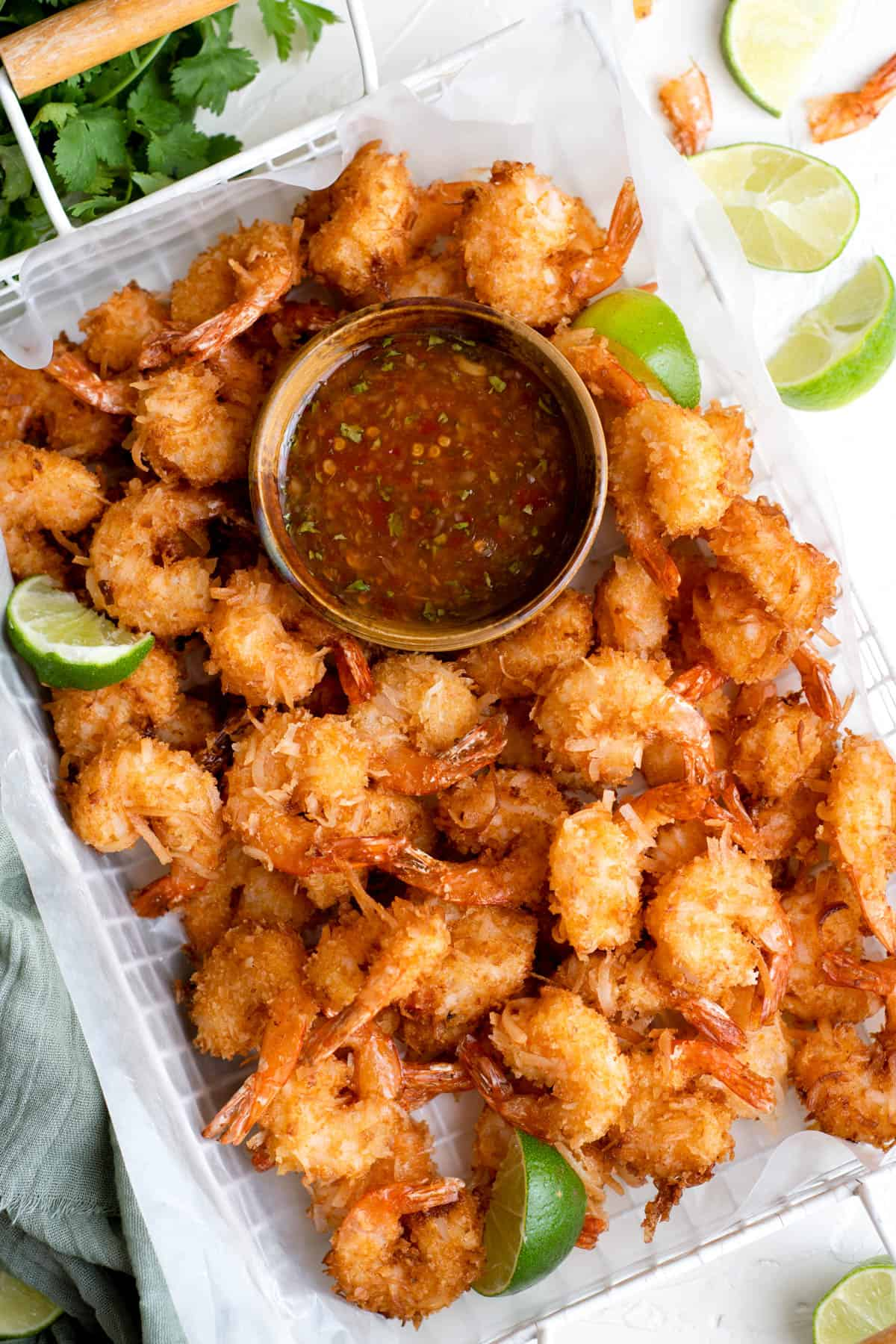 a white platter of fried coconut shrimp with a bowl of sweet chili sauce