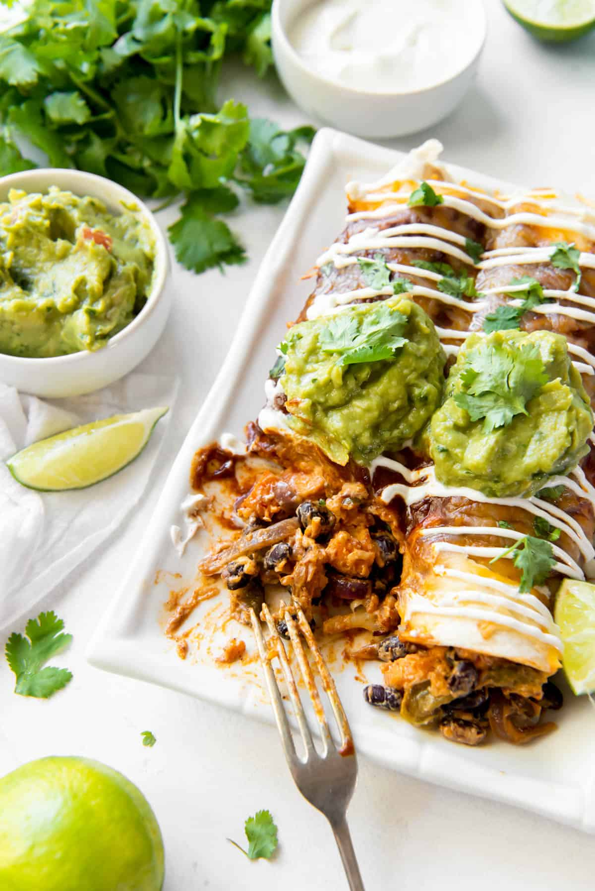 A plate with two enchiladas stuffed with veggies and beans, topped with avocado and sour cream.