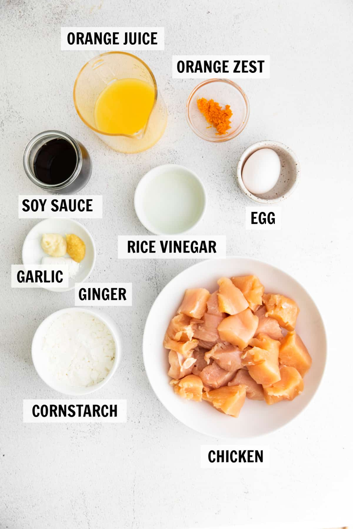 all of the ingredients for orange chicken on a white tabletop