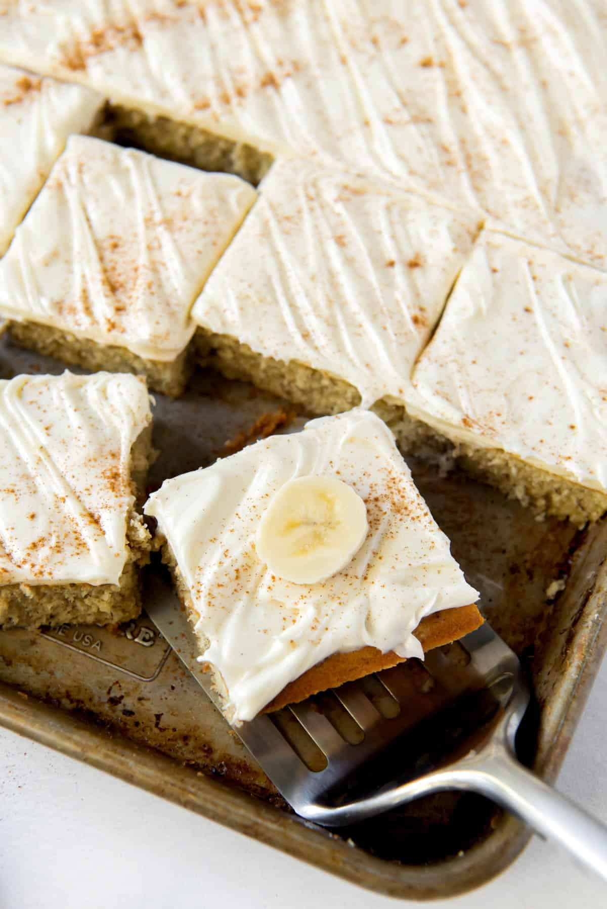 Banana bars with cream cheese on a sheet pan, one slice being served.
