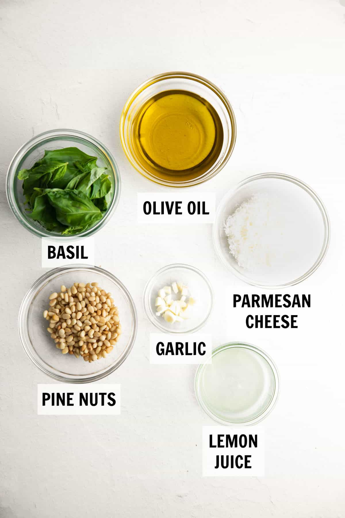 Ingredients for homemade pesto measured in glass bowls