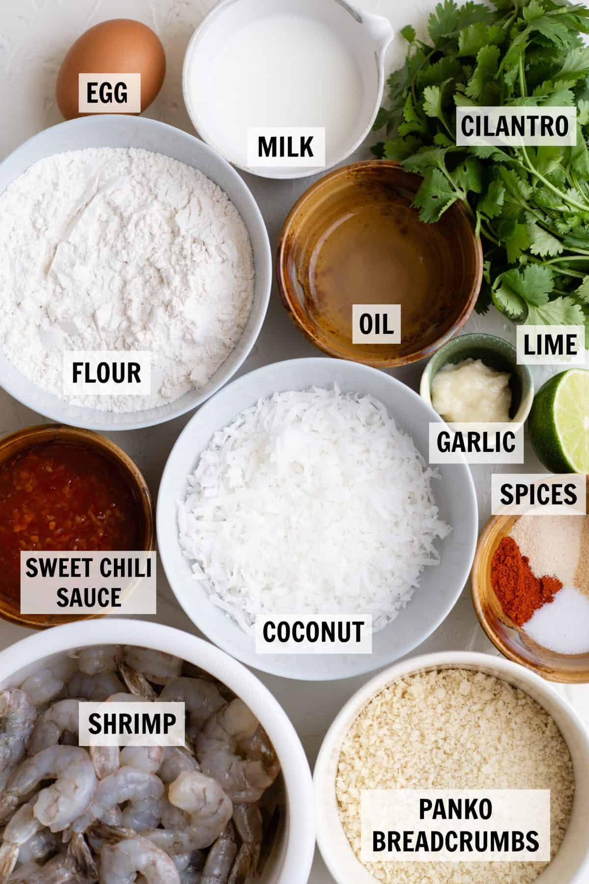 ingredients needed to make coconut shrimp measured in individual white serving dishes
