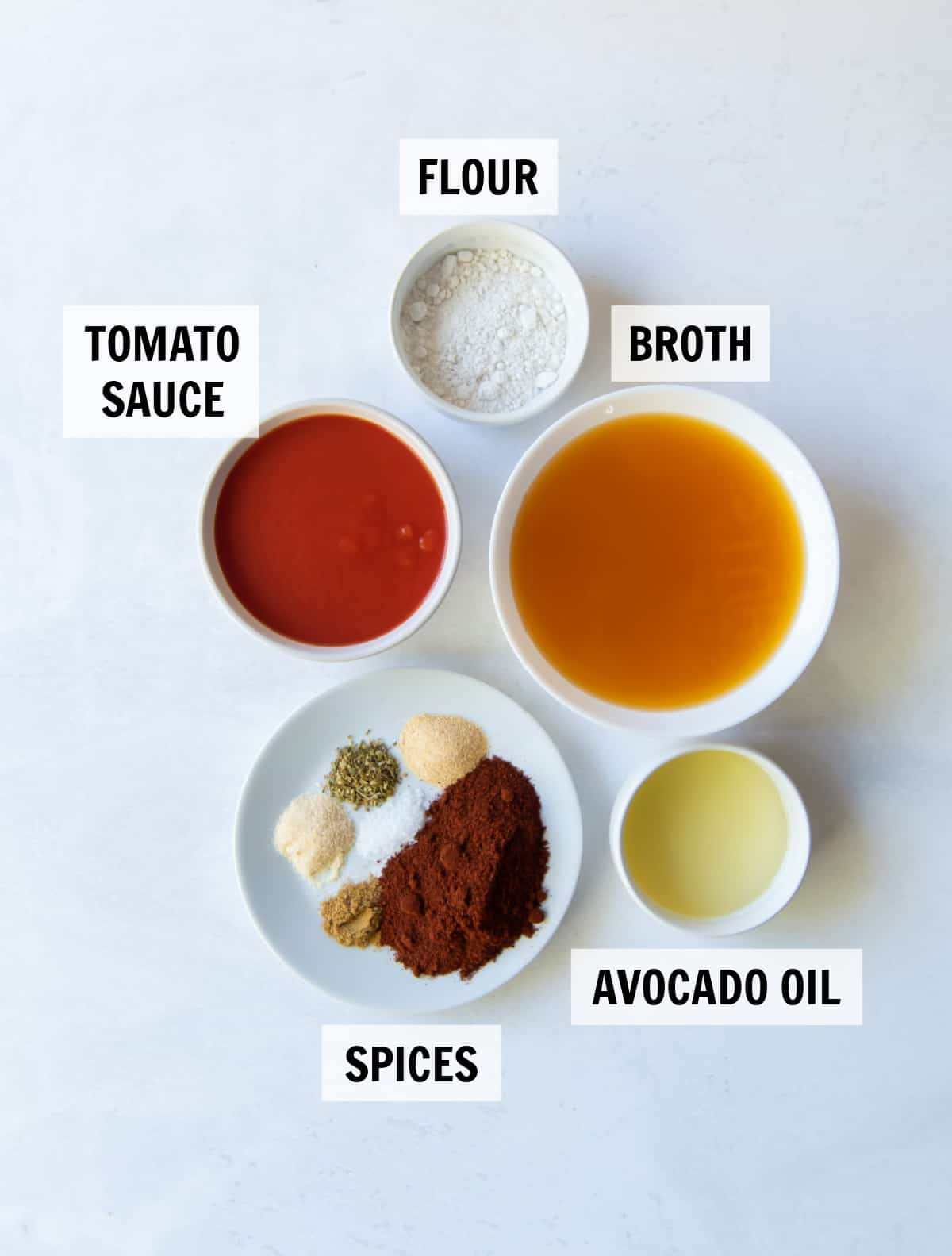 All the ingredients and spiced for easy enchilada sauce measured in white bowls