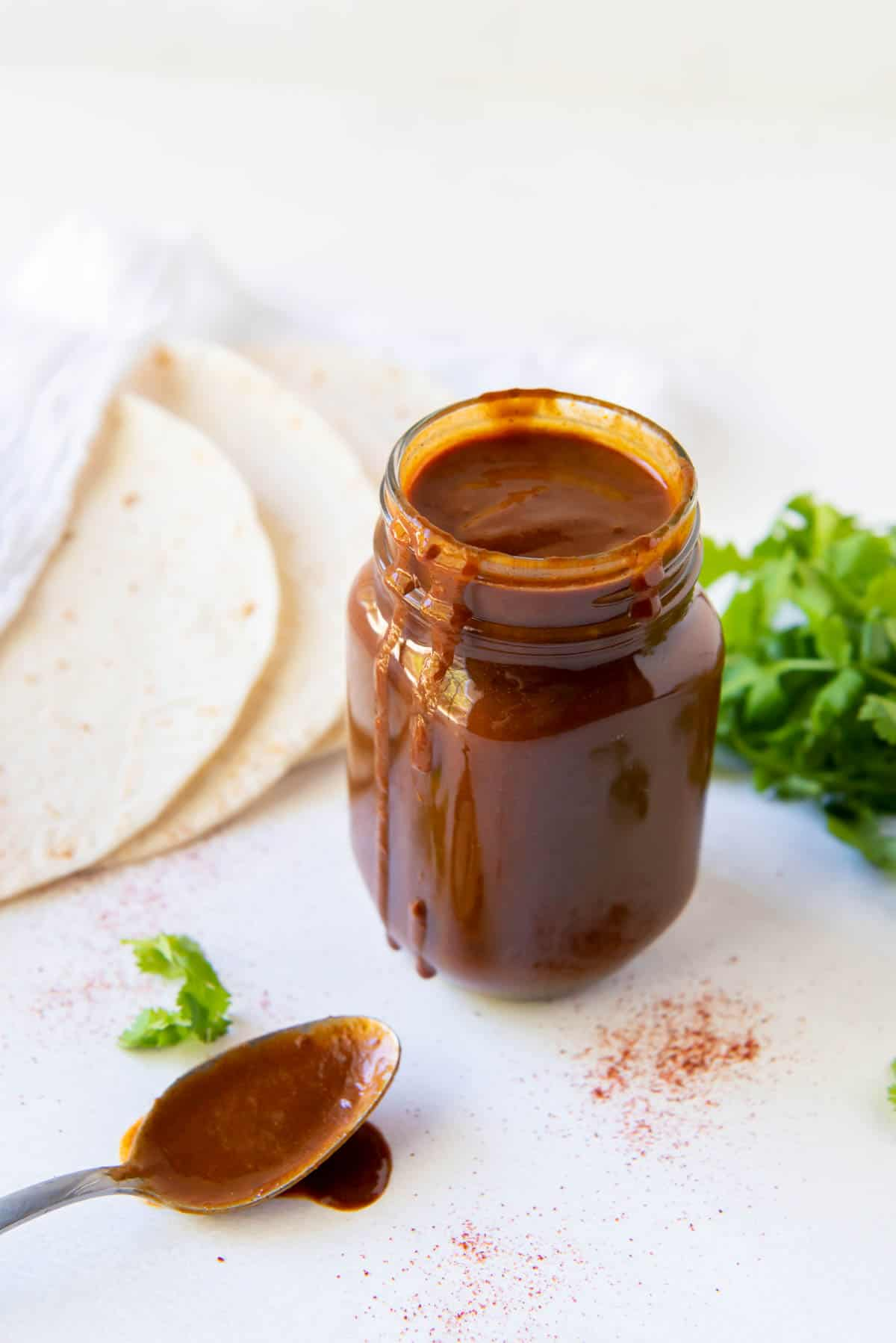 Homemade enchilada sauce in a glass jar with tortillas in the background and a spoon of sauce in front.
