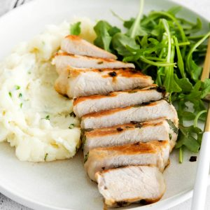 sliced bonless pork chop on a plate with arugula and mashed potatoes