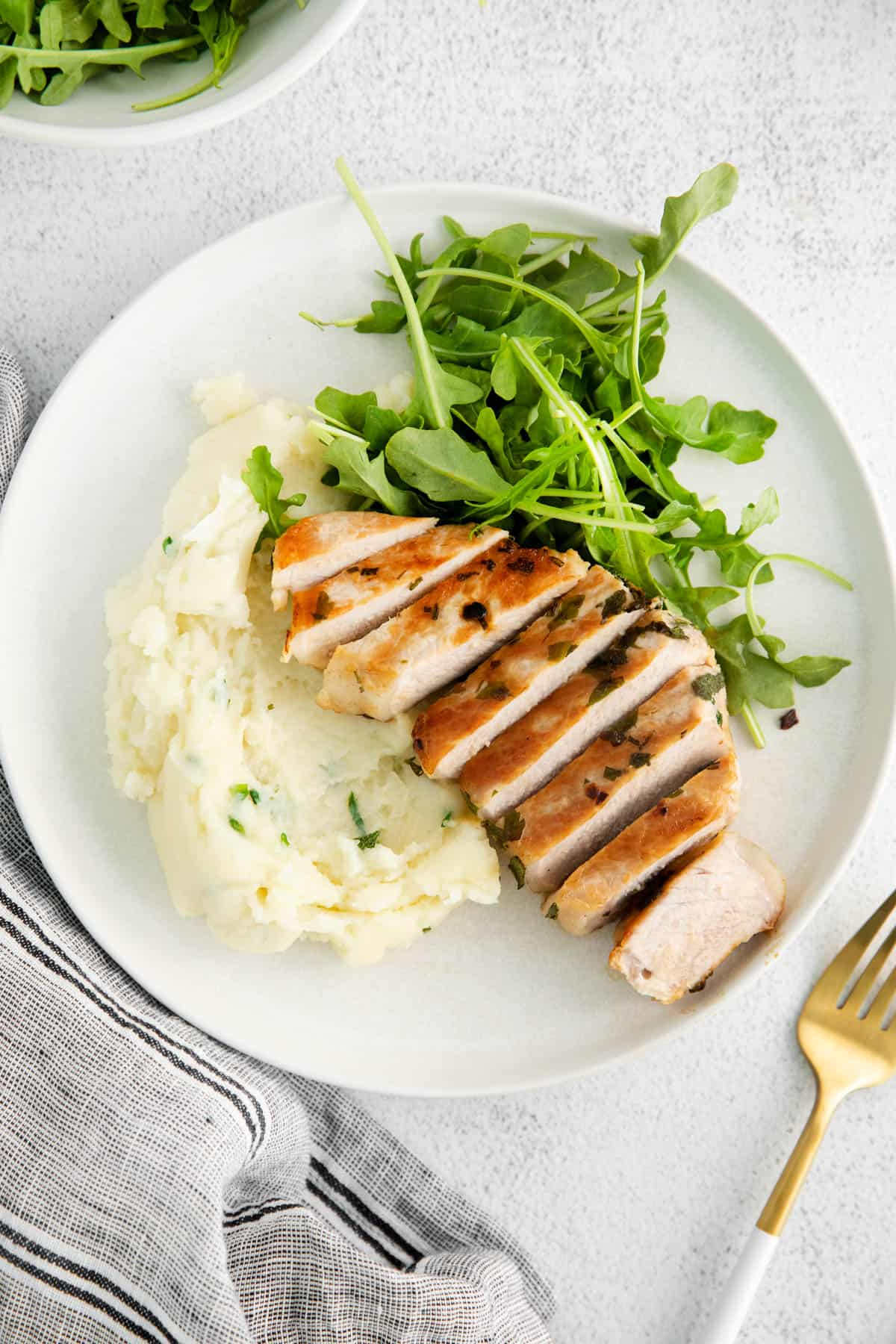 one cut pork chop on a plate with mashed potatoes and greens