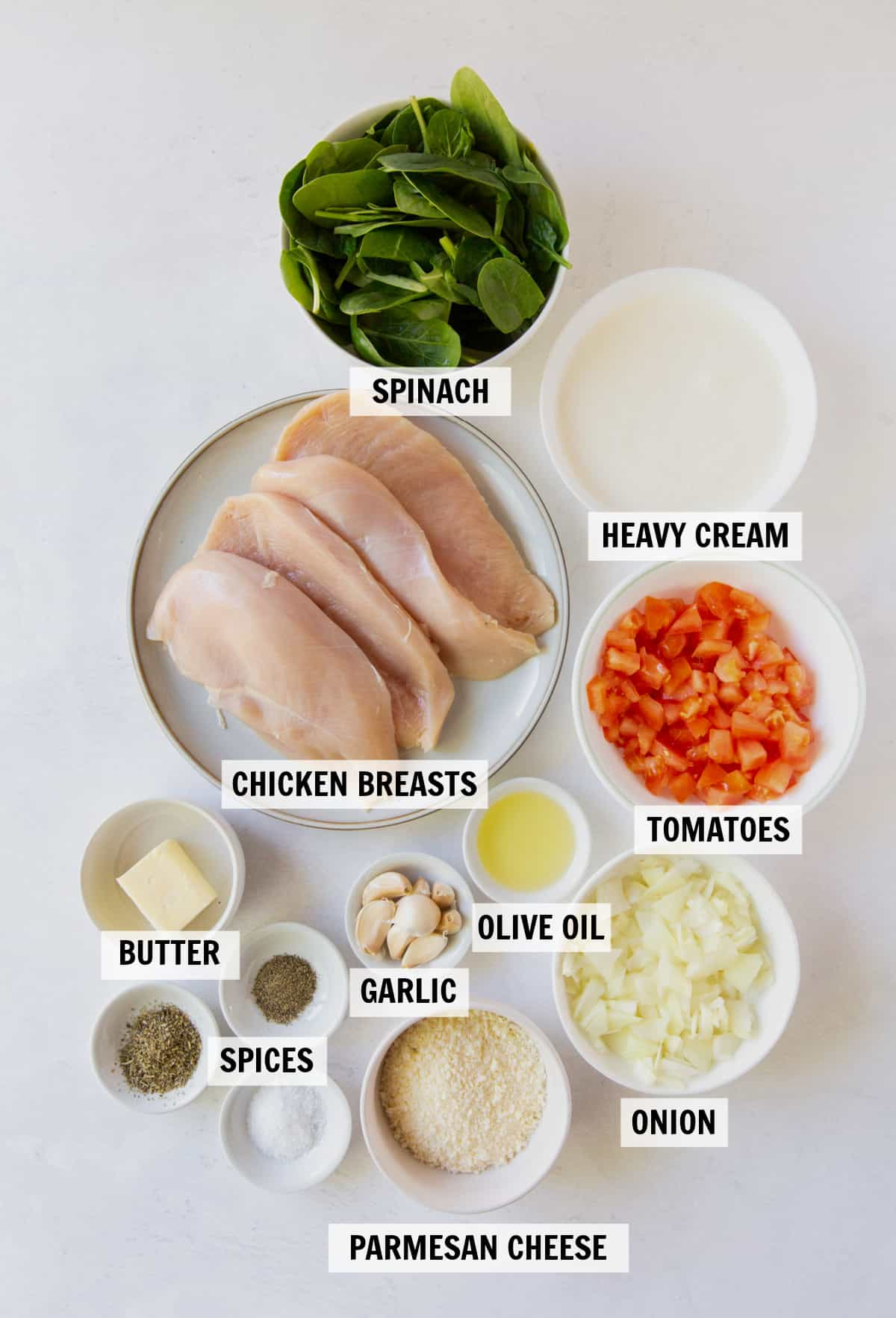 ingredients for tuscan garlic chicken in bowls on a white tabletop