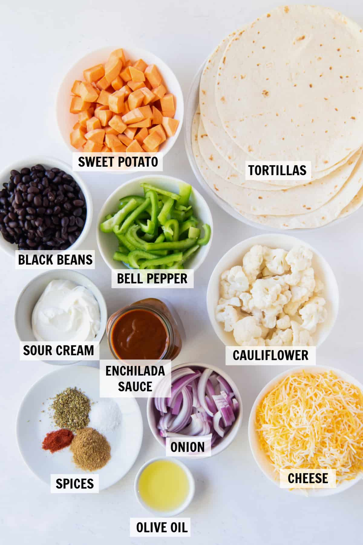 The ingredients to make vegetable enchiladas measured out in small white bowls.