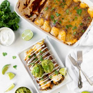 Aerial view of a pan of veggie enchiladas and a plate with two vegetable enchiladas, topped with guacamole and sour cream.