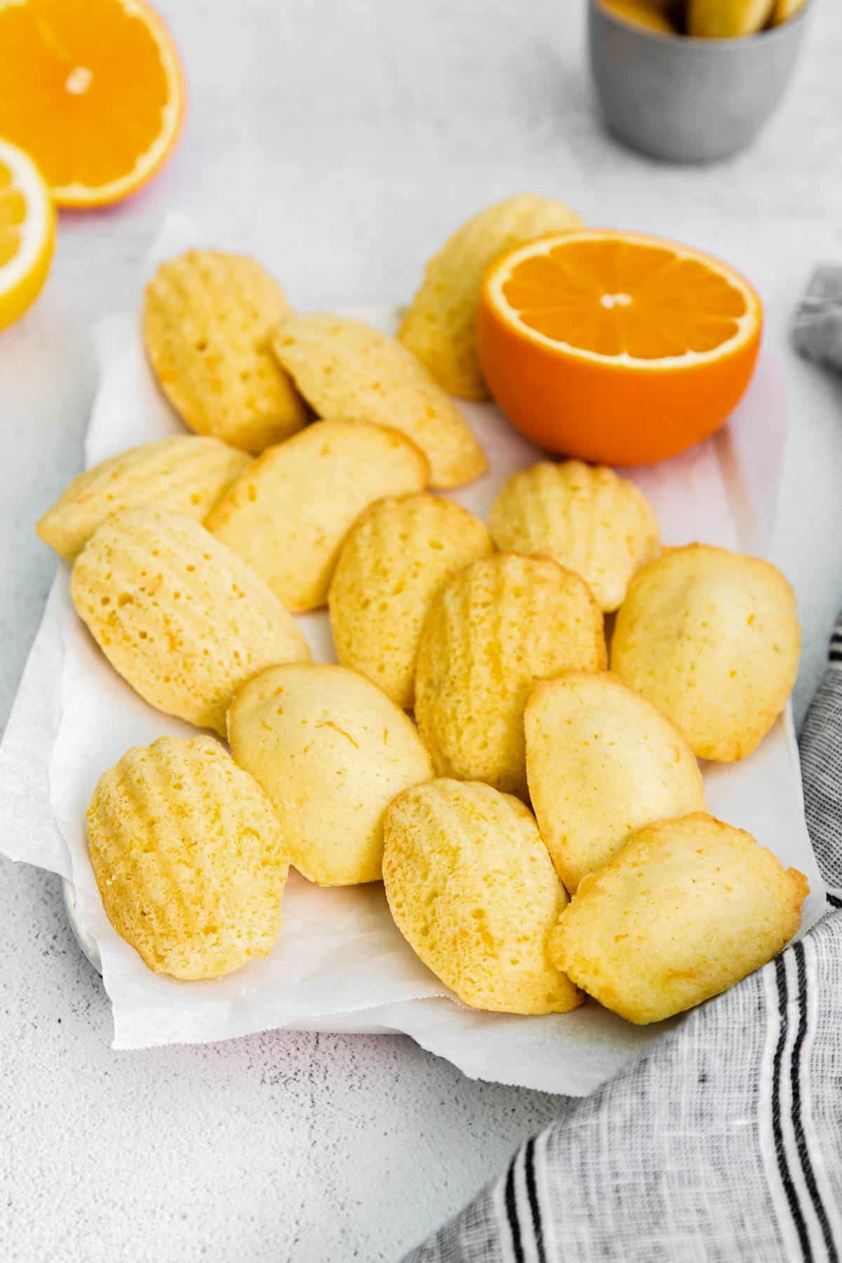 baked citrus madeleines sitting on a piece of parchment paper