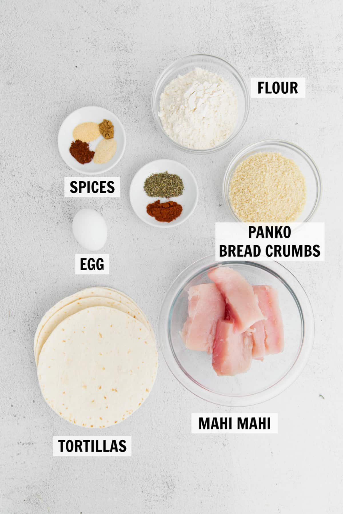 all of the ingredients for fish tacos on a white table