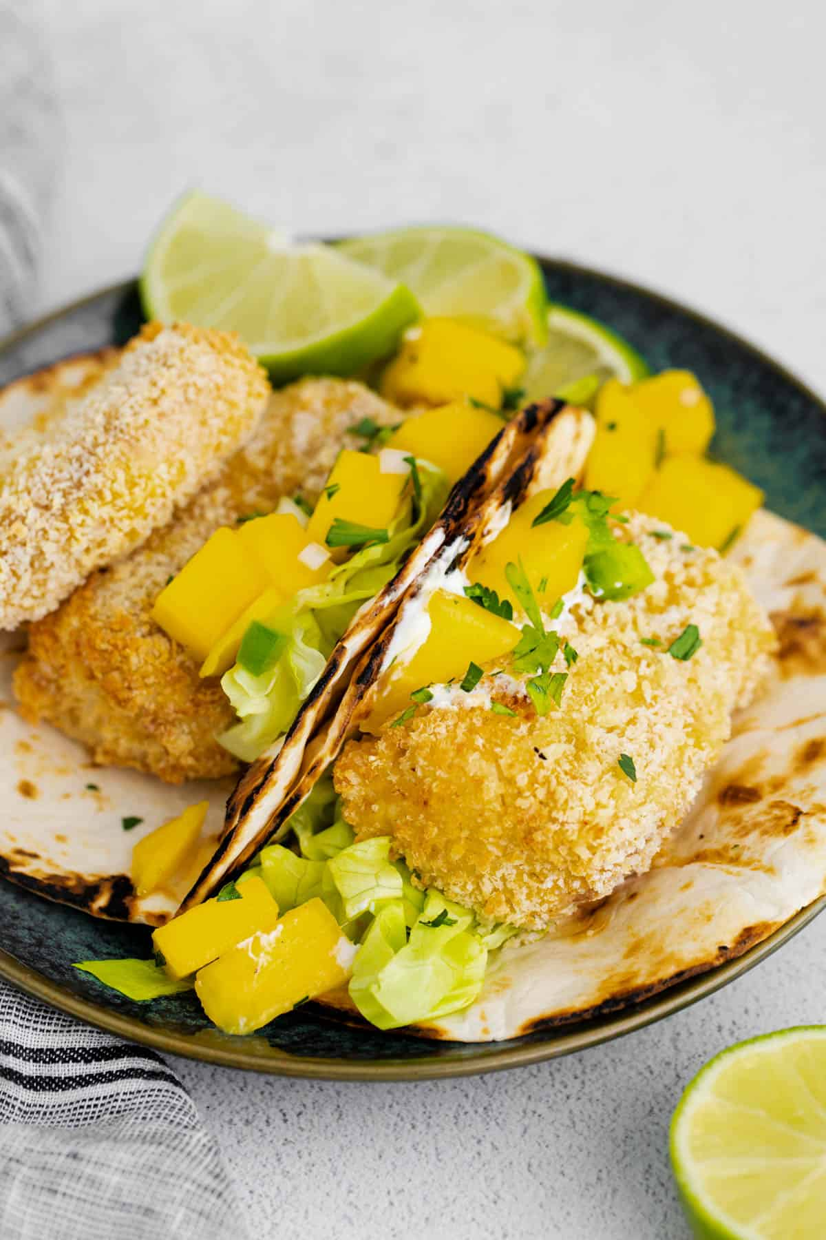 two air fryer fish tacos on a plate with fresh mango salsa on top