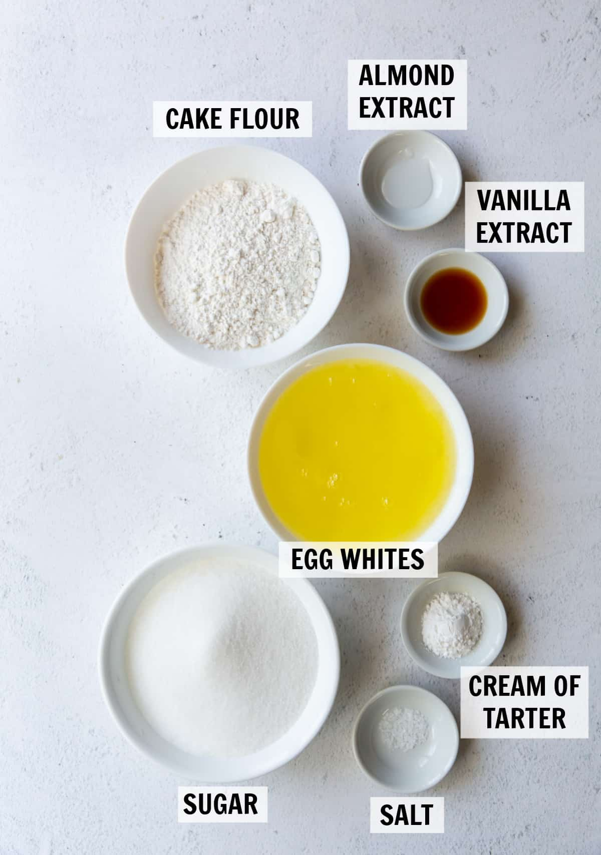 Ingredients needed to make angel food cake measured in small white dishes