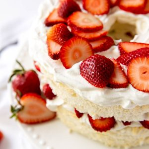 Angel food layer cake topped with strawberries and whipped cream
