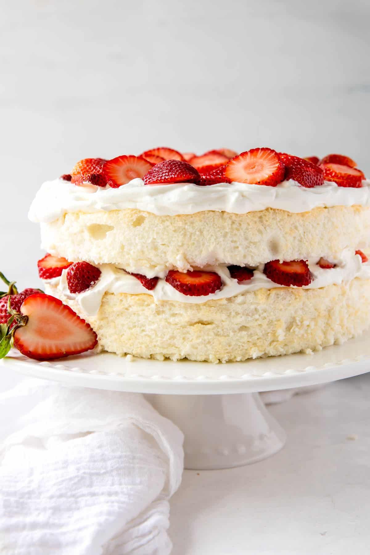 Angel food cake with layers of whipped cream and strawberries