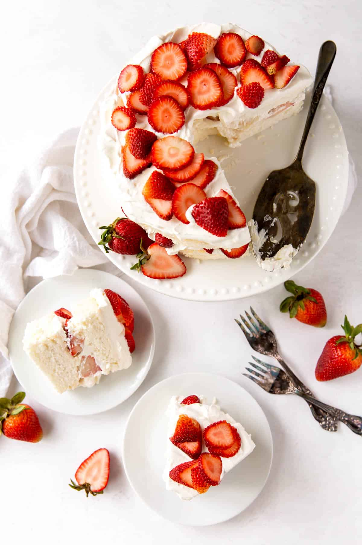 Aerial view of the best angel food cake, with two slices cut on serving plates, topped with fresh strawberries