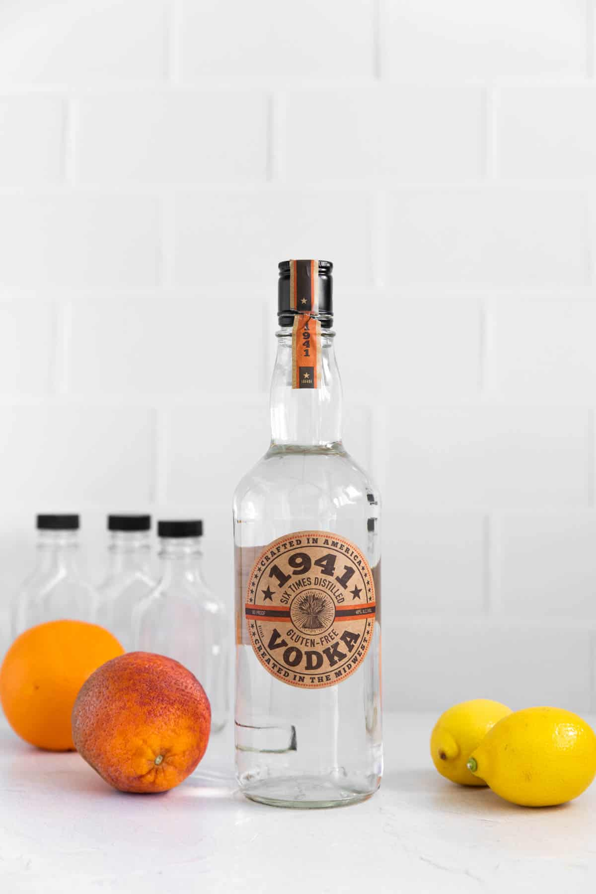 a bottle of vodka and citrus fruit for the recipe