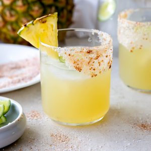 mezcal margarita in a glass with a salted rim and pineapple slice