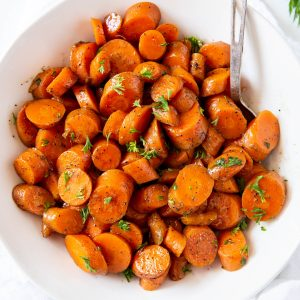 A bowl of sauteed carrots with parsley