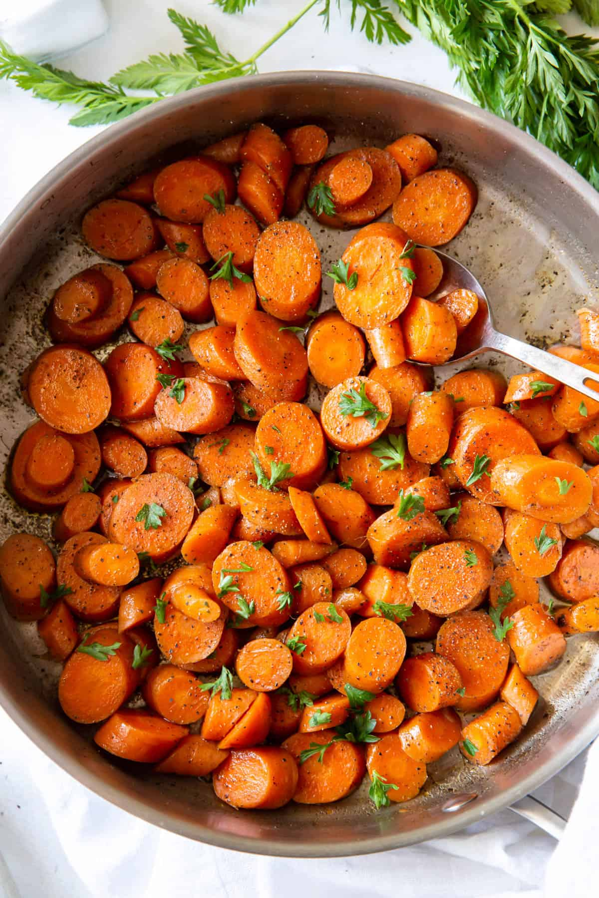 Sauteed carrots topped with parsley in a silver pan