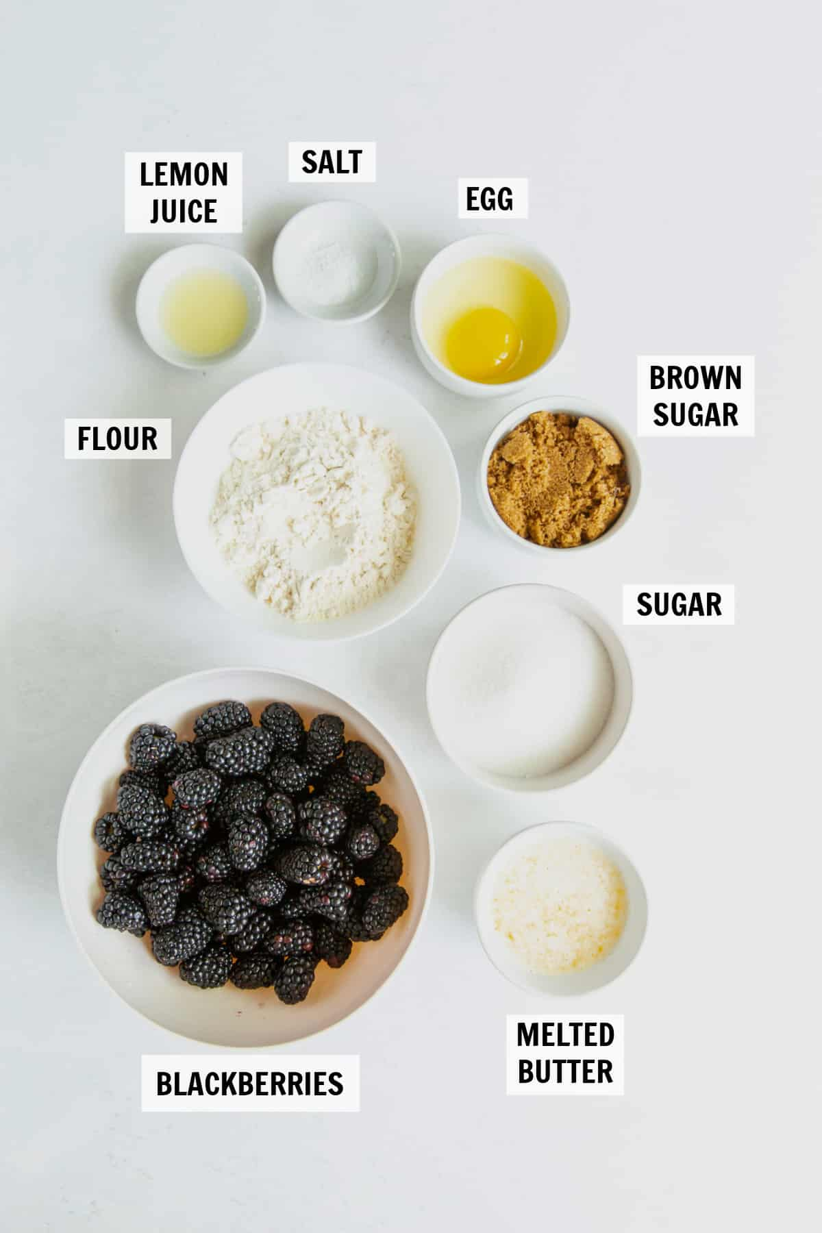 all of the ingredients for blackberry cobbler on a white countertop