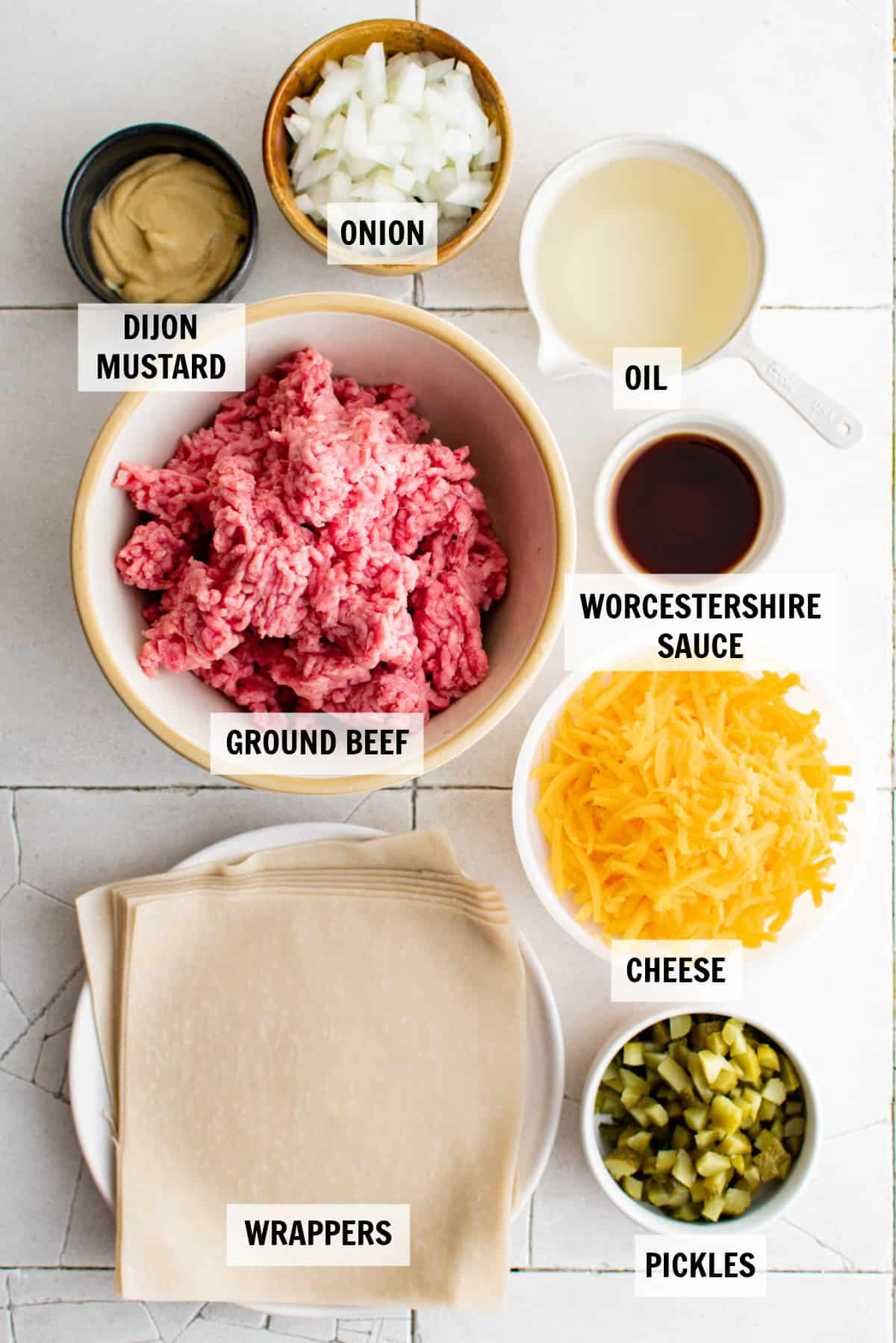 all of the ingredients for cheeseburger egg rolls on a countertop