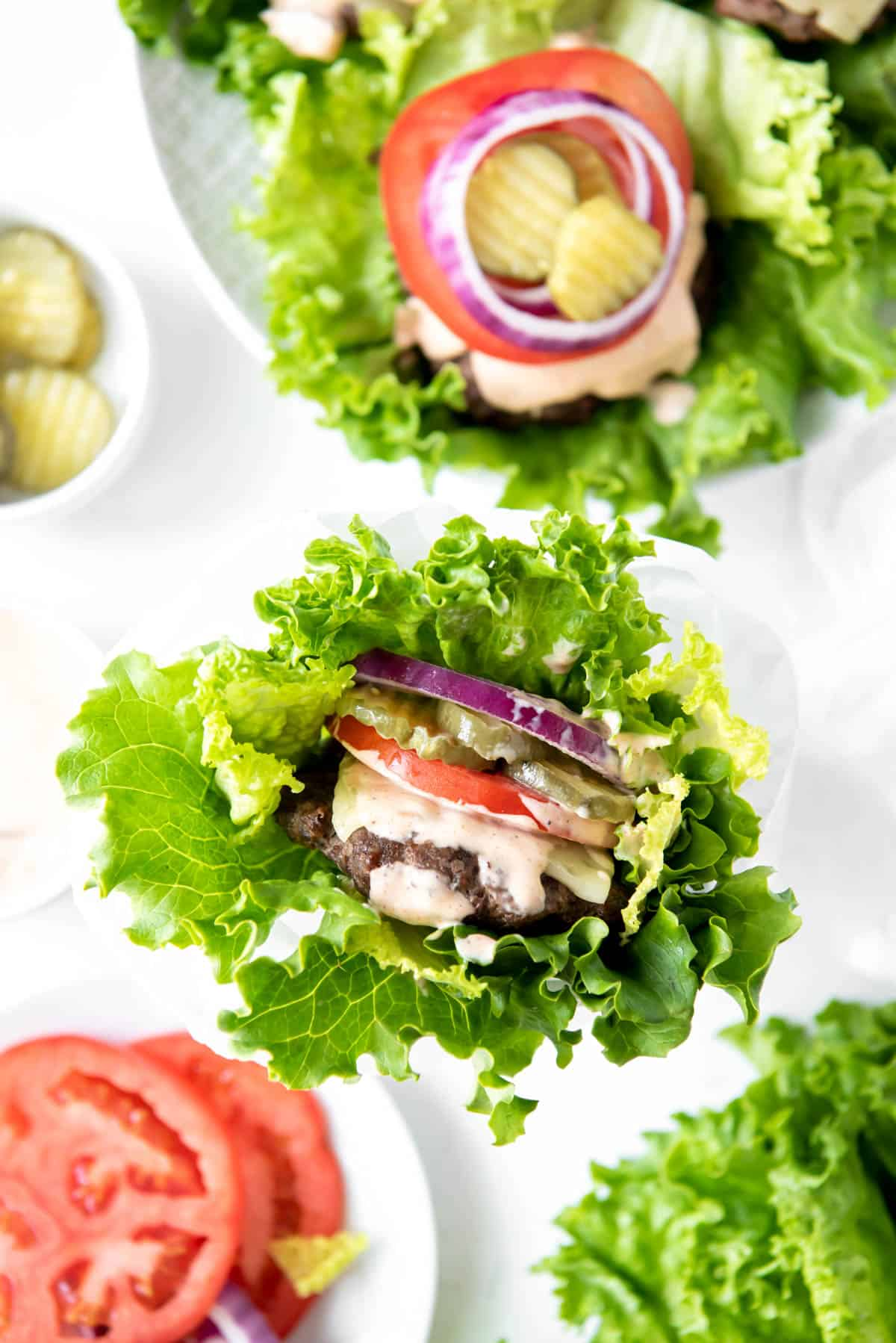 burger with homemade burger sauce, tomato and onion in a lettuce wrap