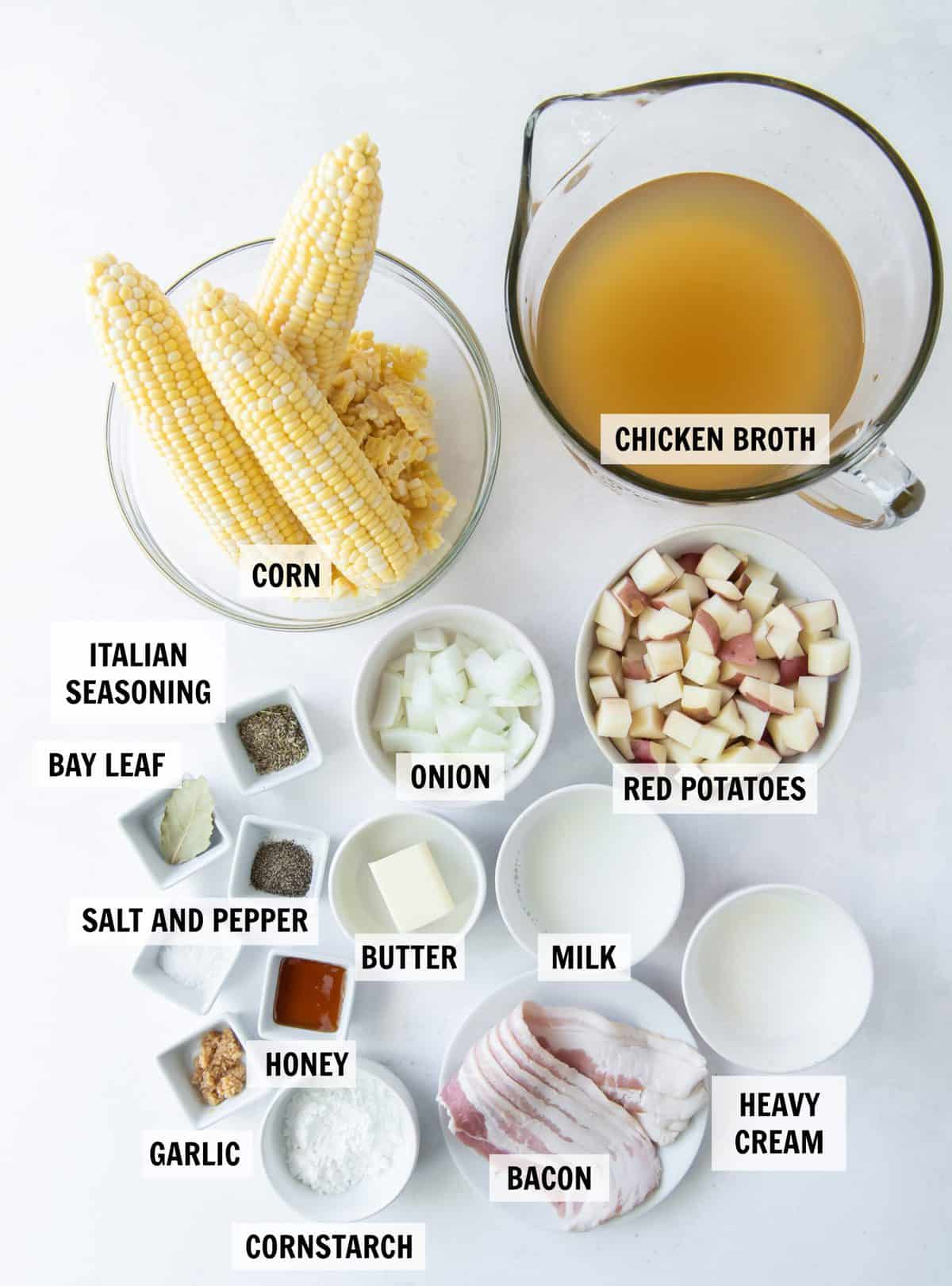 all of the ingredients for corn chowder on a white tabletop