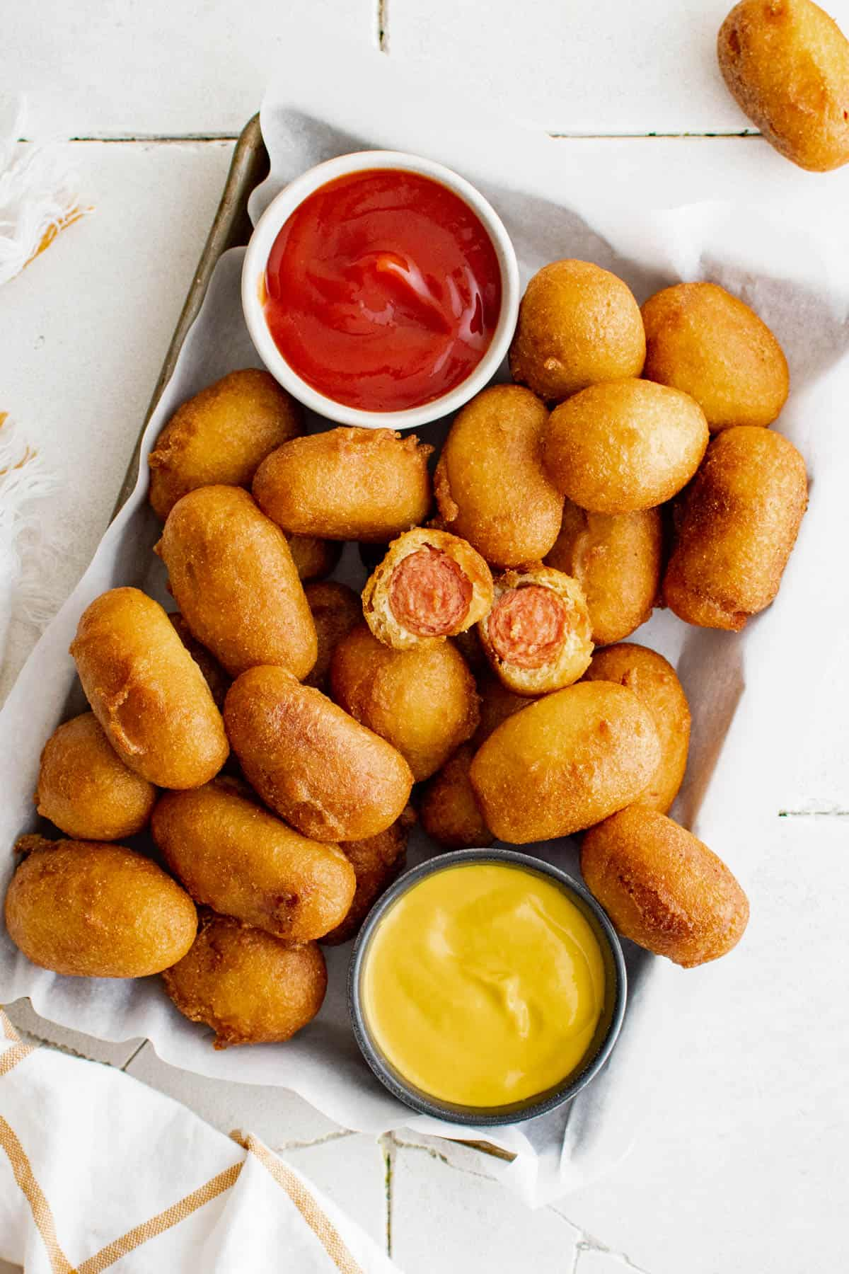 mini corn dogs on a tray with ketchup and mustard