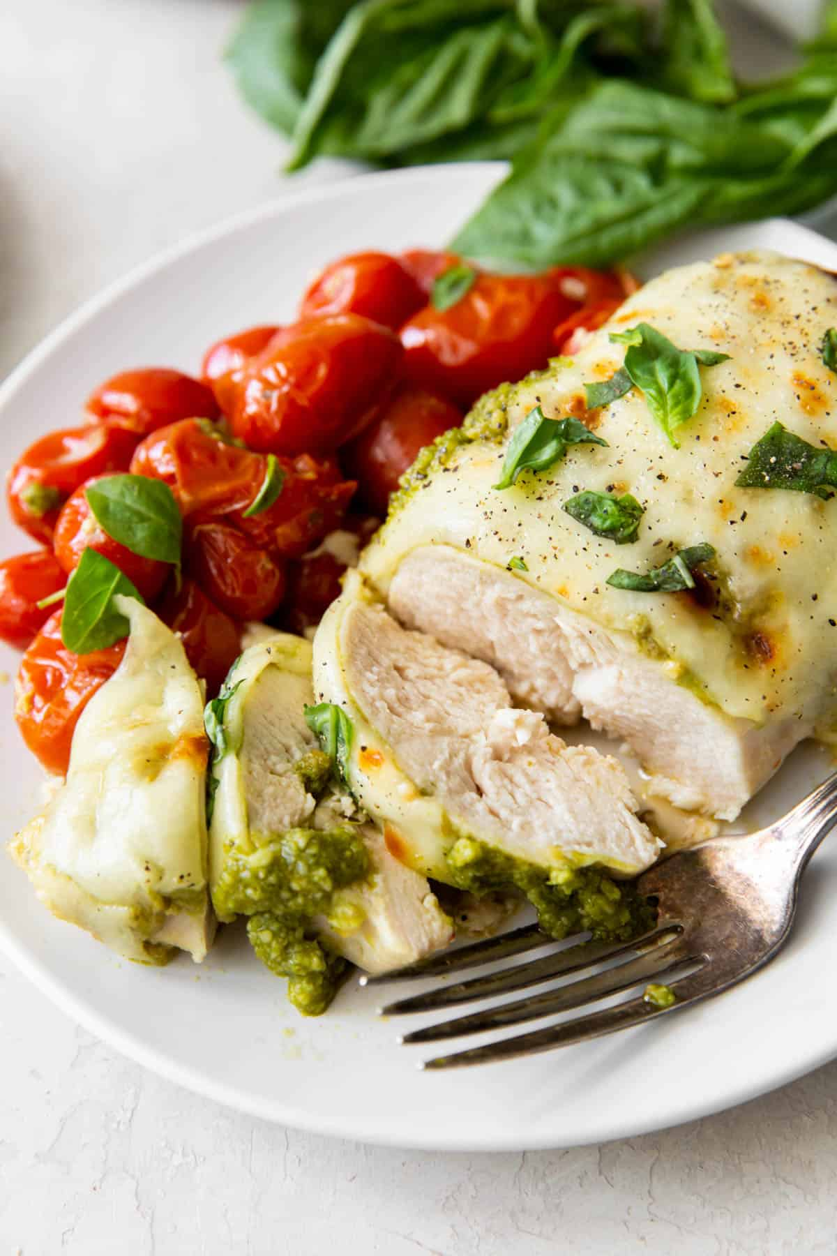 sliced pesto chicken on a plate with roasted tomatoes