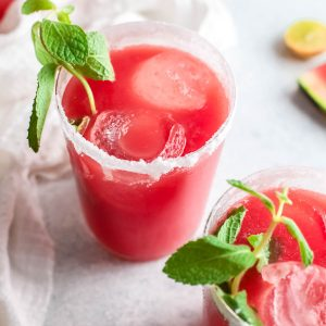 a glass of watermelon paloma with spring of fresh mint