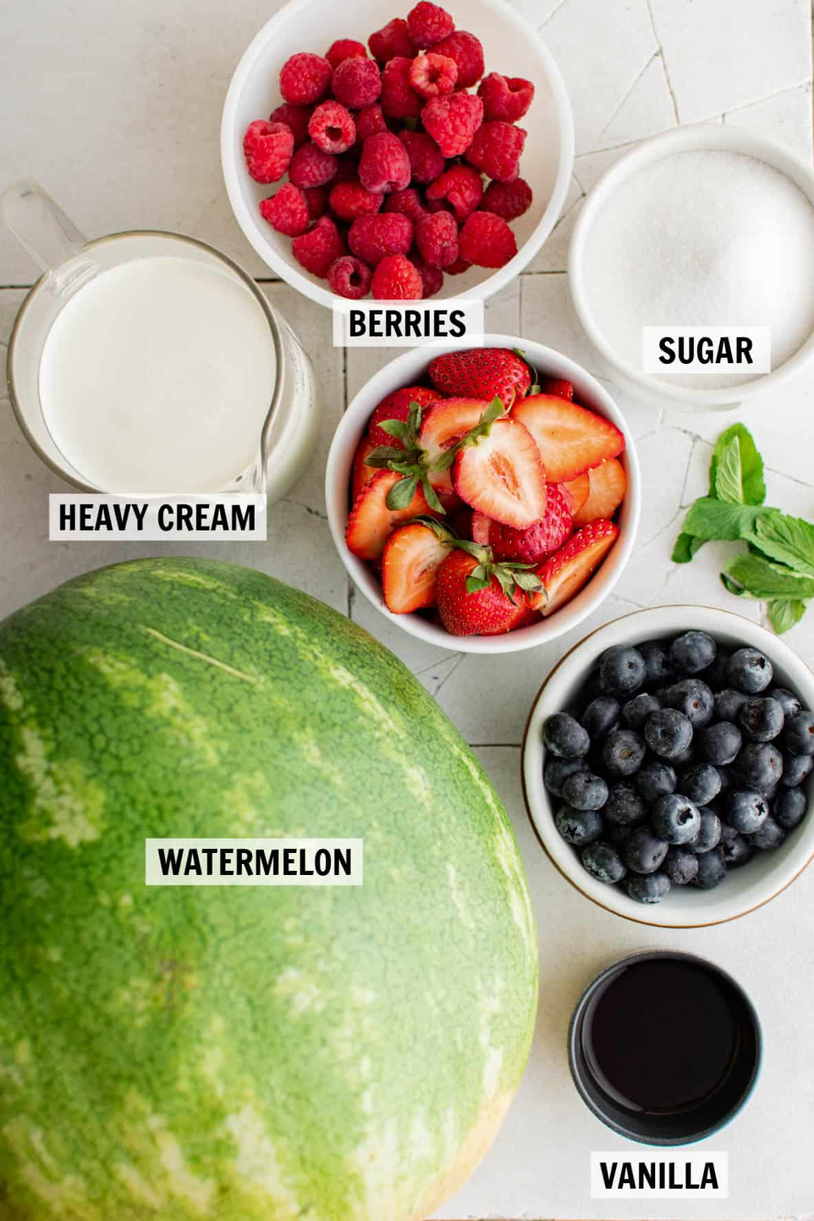 all of the ingredients for watermelon cake on a white countertop