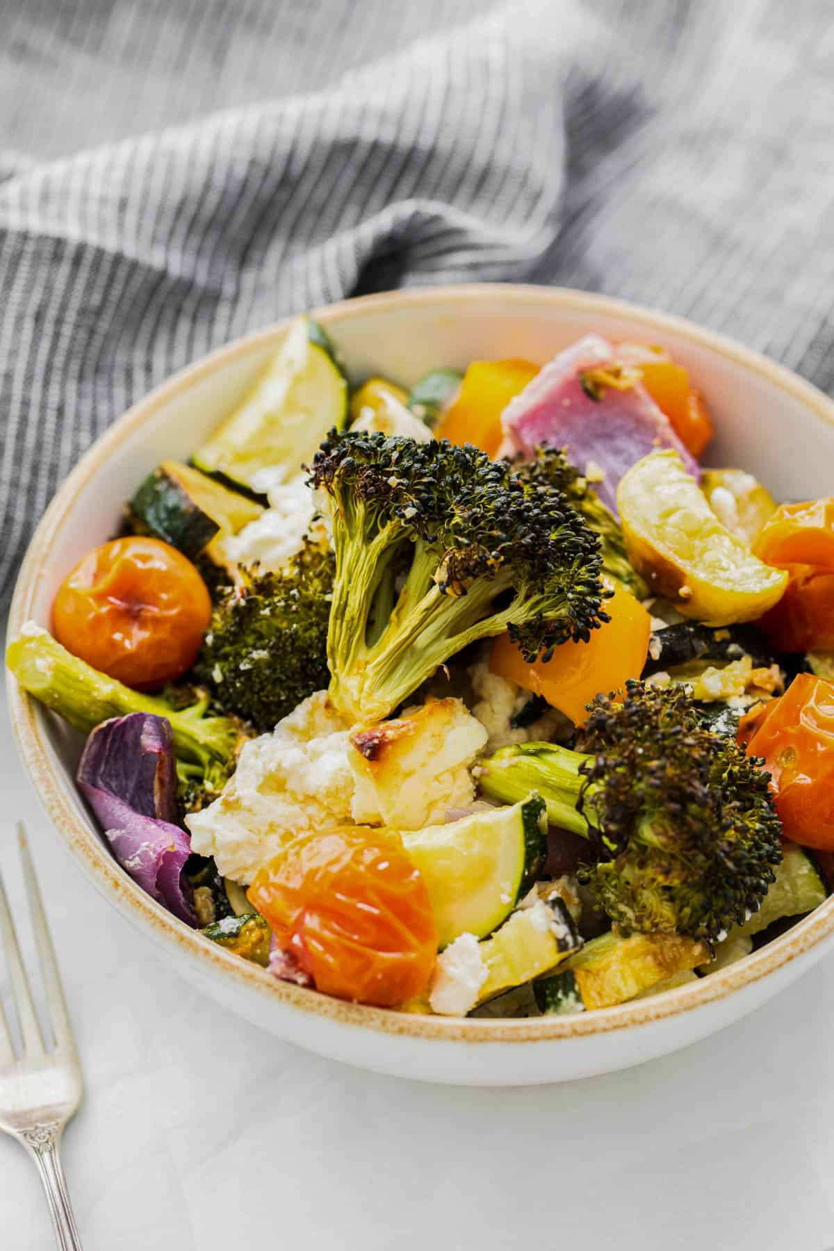 all of the roasted veggies in a bowl with feta