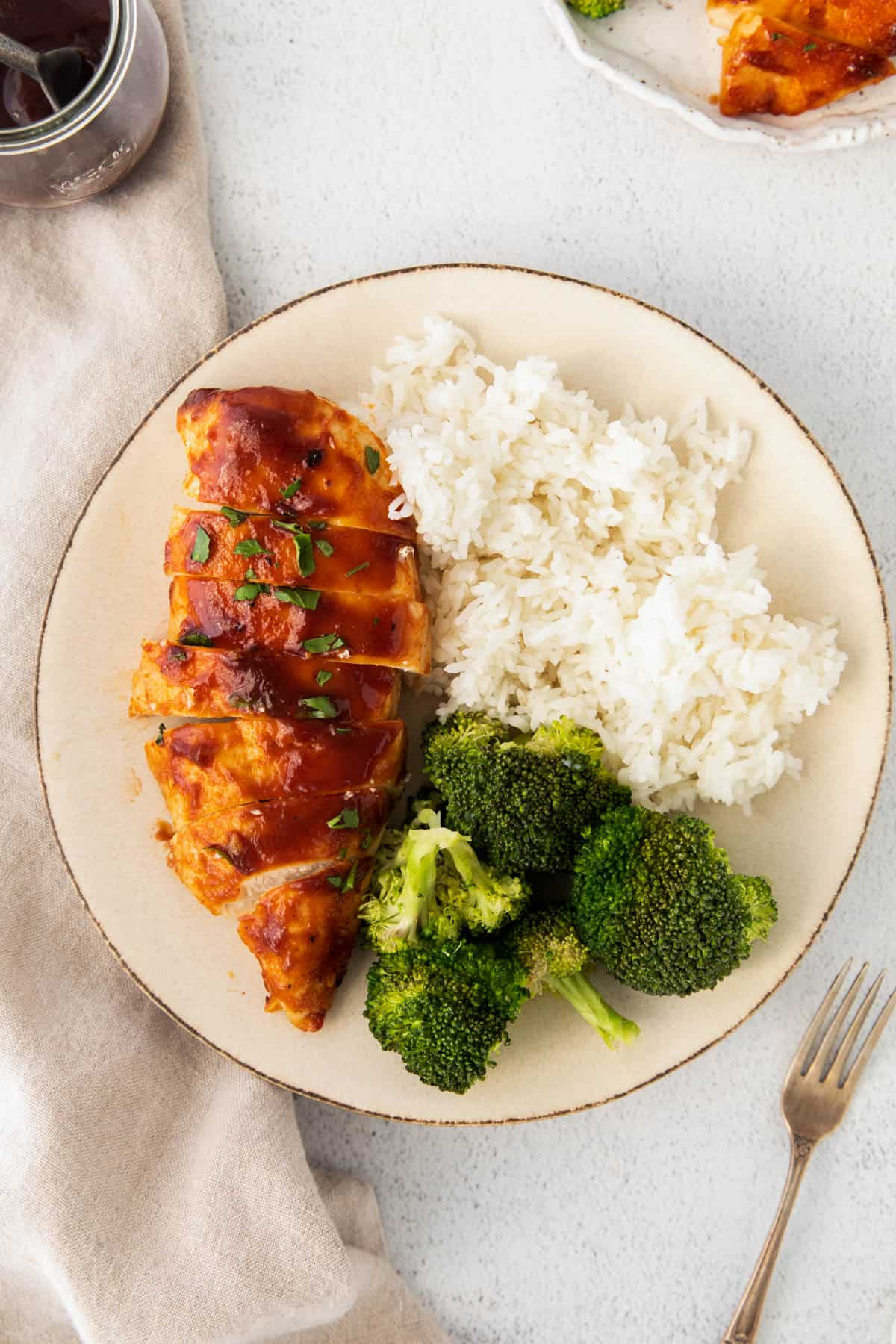 one piece of air fried bbq chicken on plate with rice and broccoli