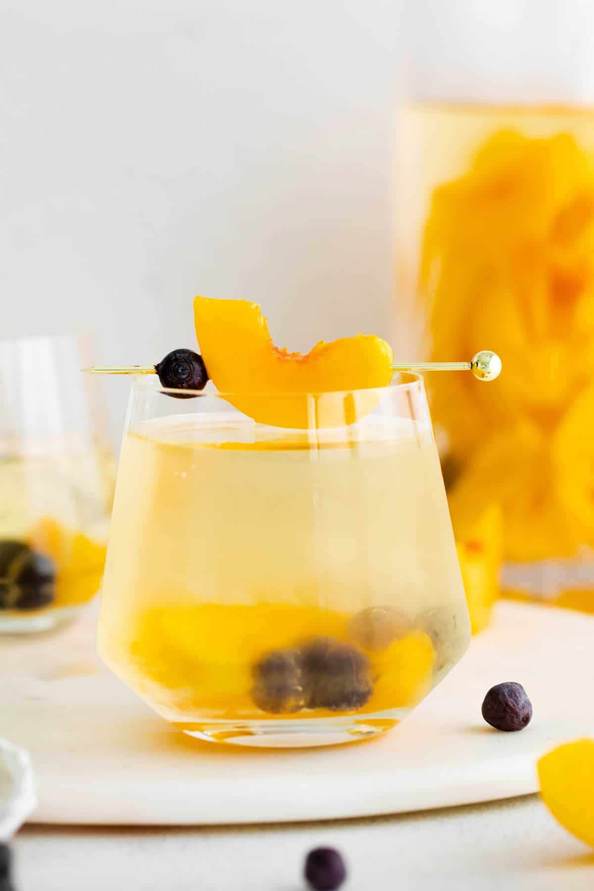 glass of peach sangria garnished with fresh peach slices