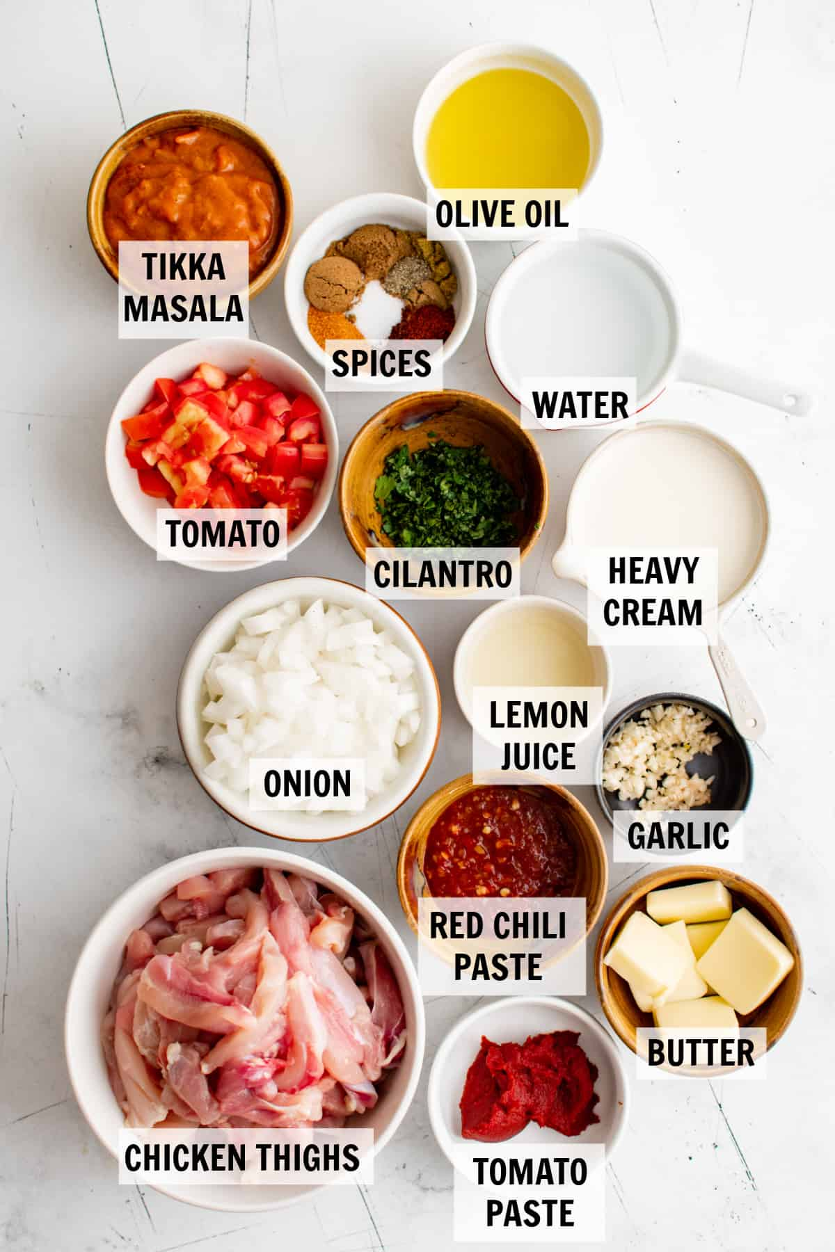 all of the ingredients for butter chicken on a white tabletop
