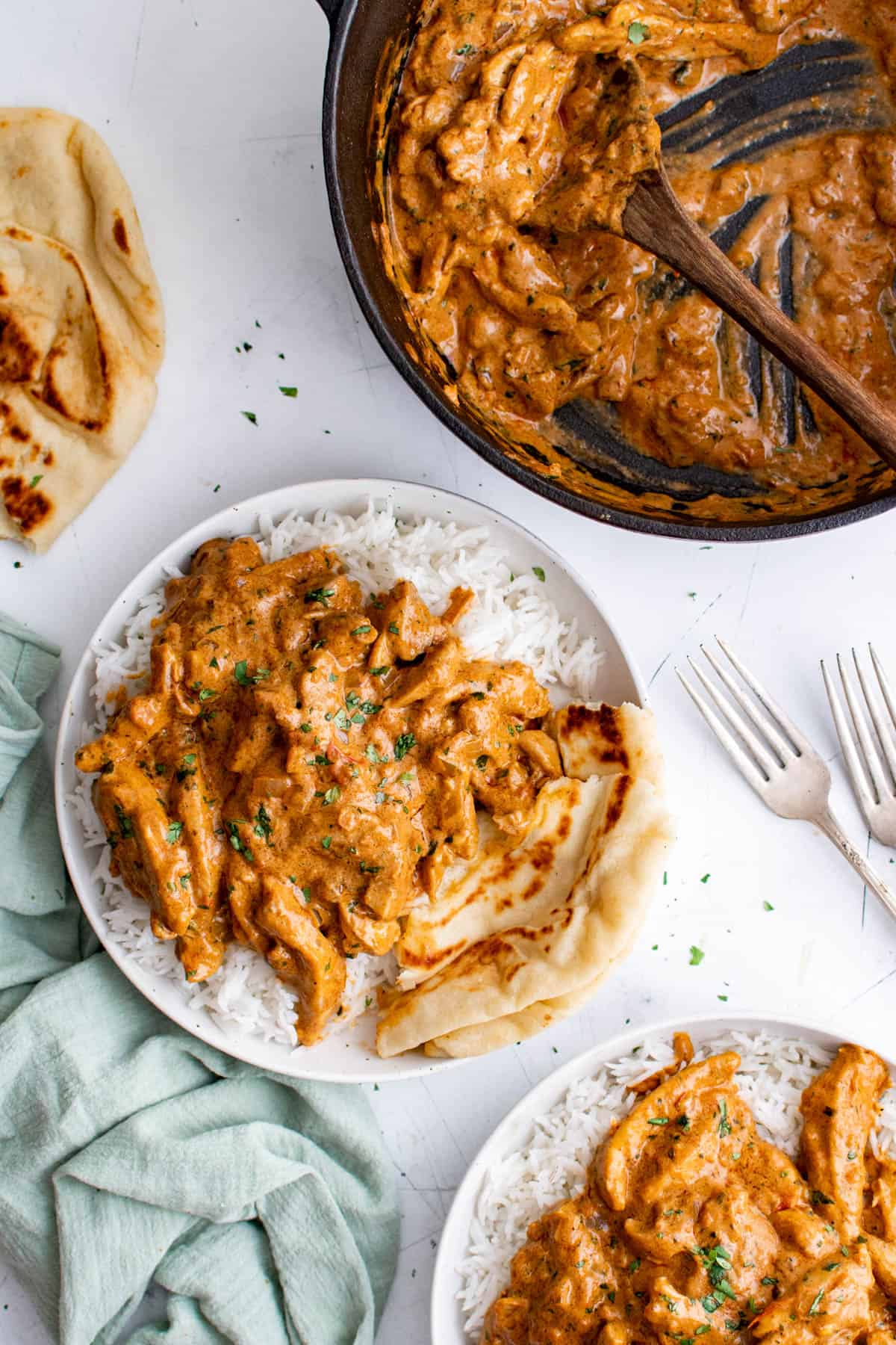 two plates of indian butter chicken on a tabletop with a pan
