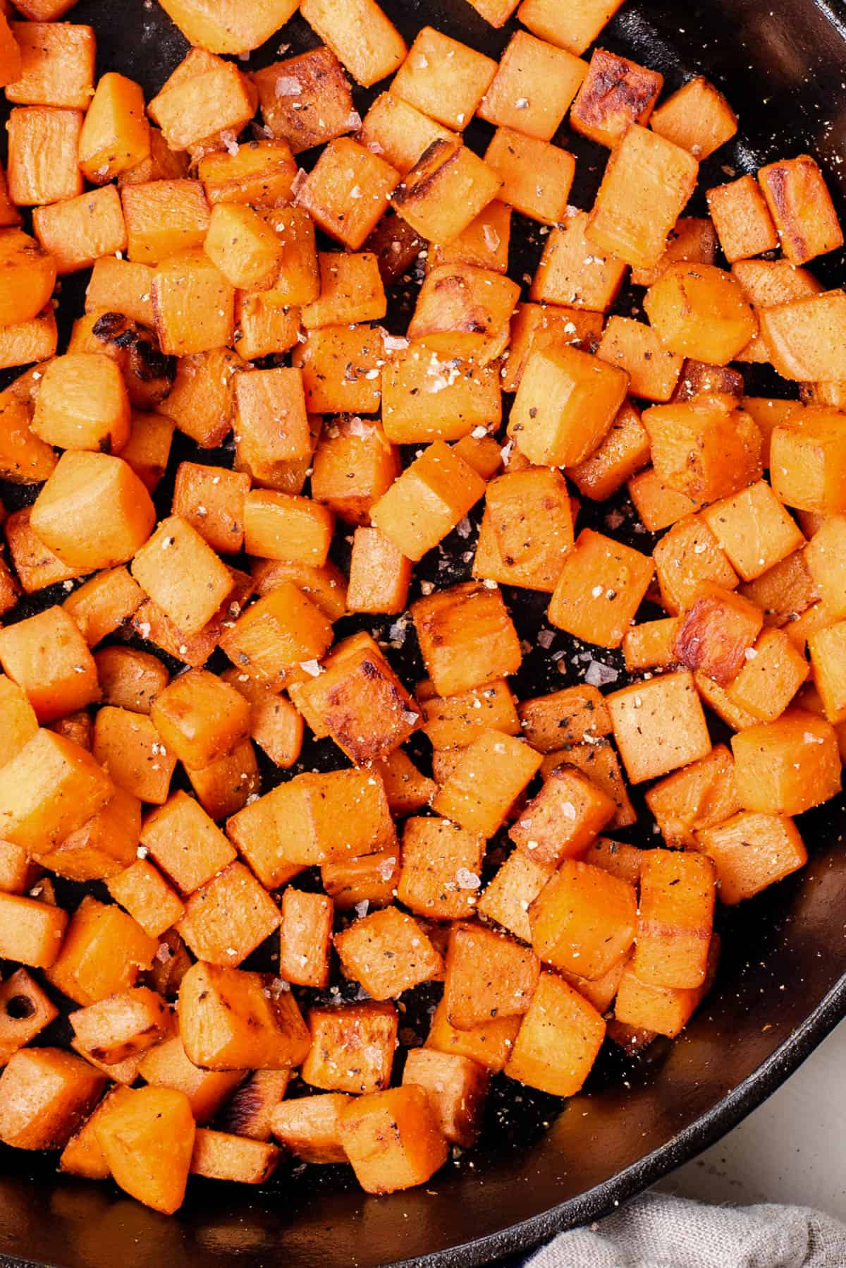 a skillet with sauteed sweet potatoes