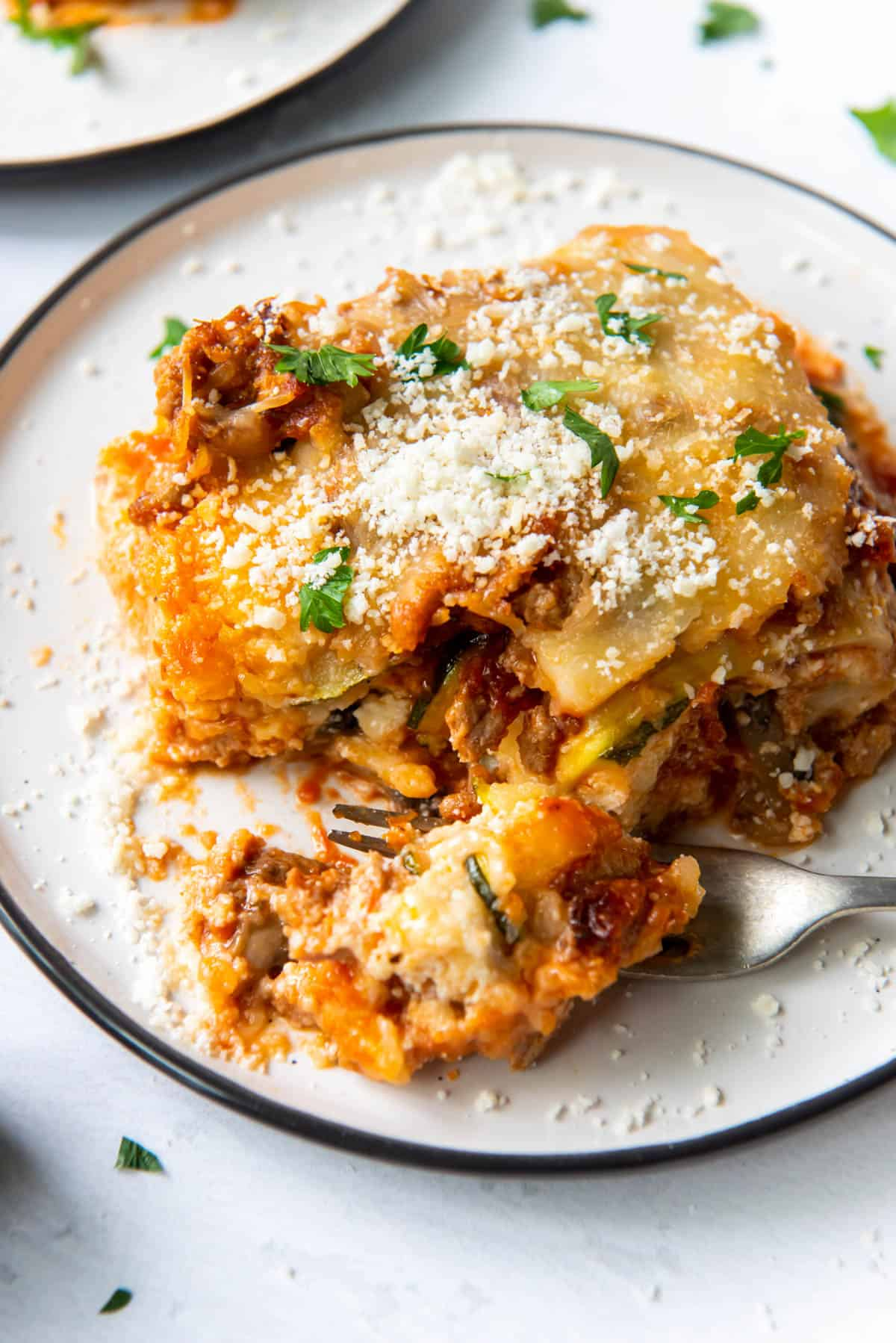 a slice of zucchini lasagna on a plate with a bite taken out with a fork