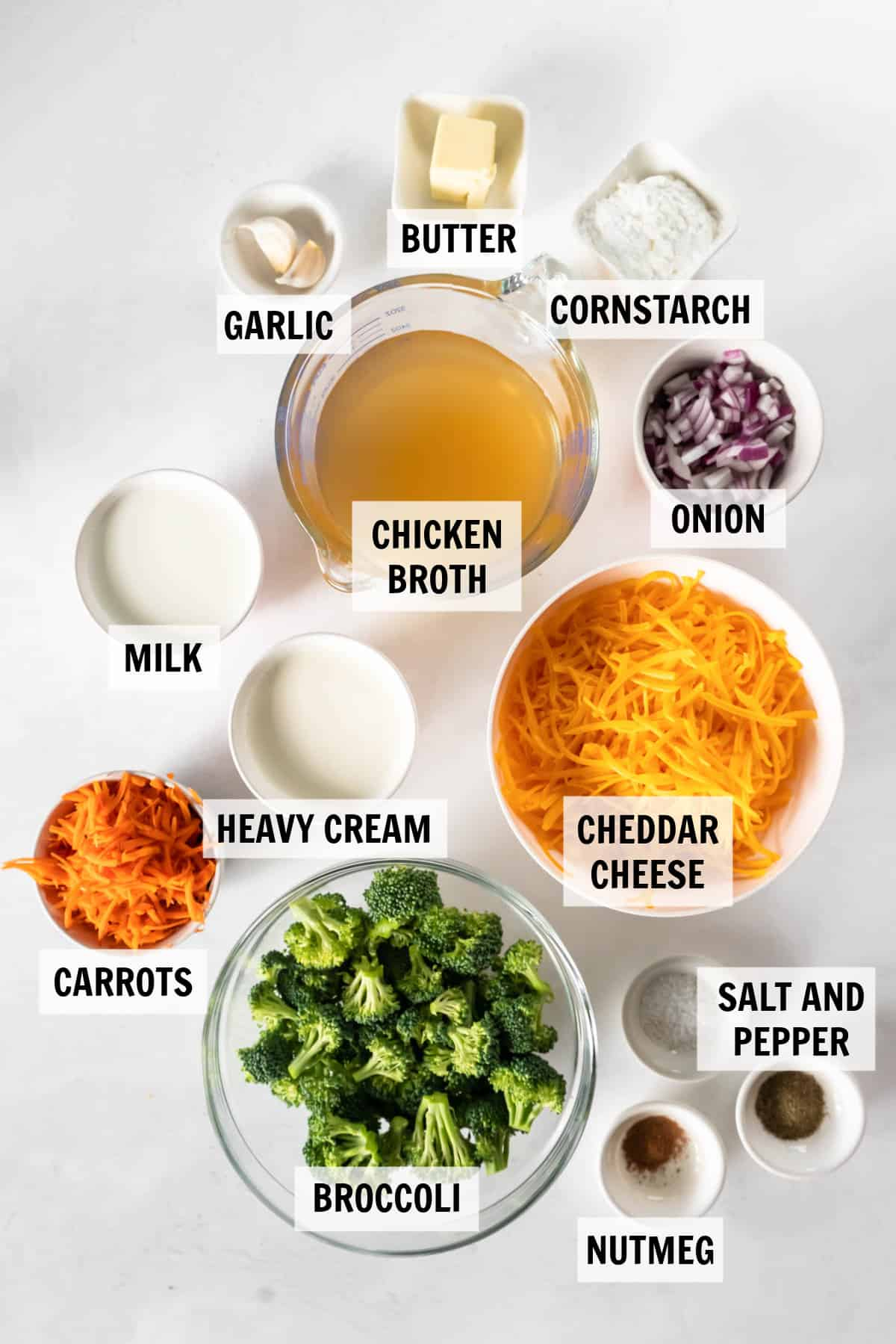 all of the ingredients for broccoli cheddar soup on a white countertop