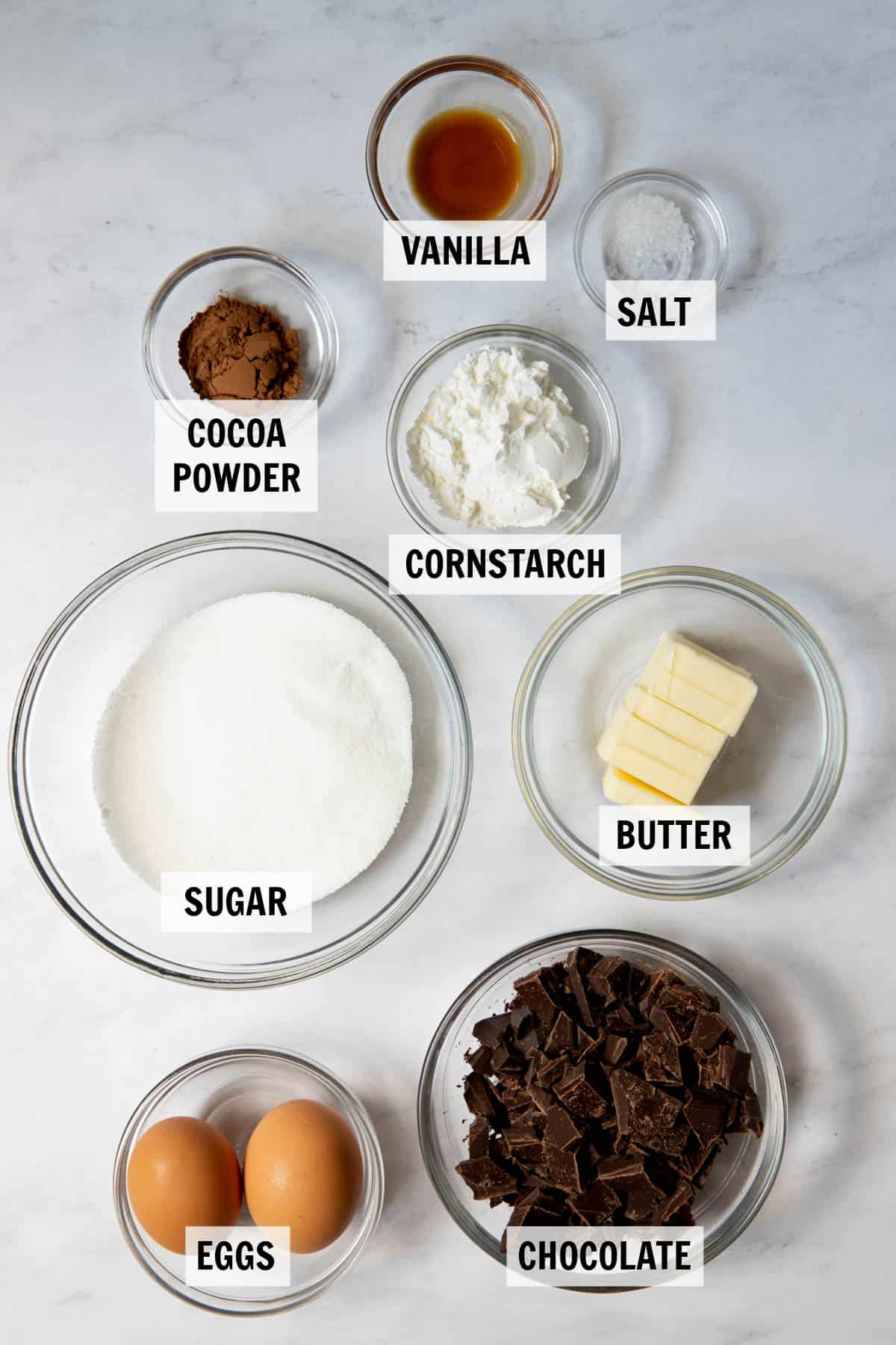 all of the ingredients for flourless brownies on a white countertop