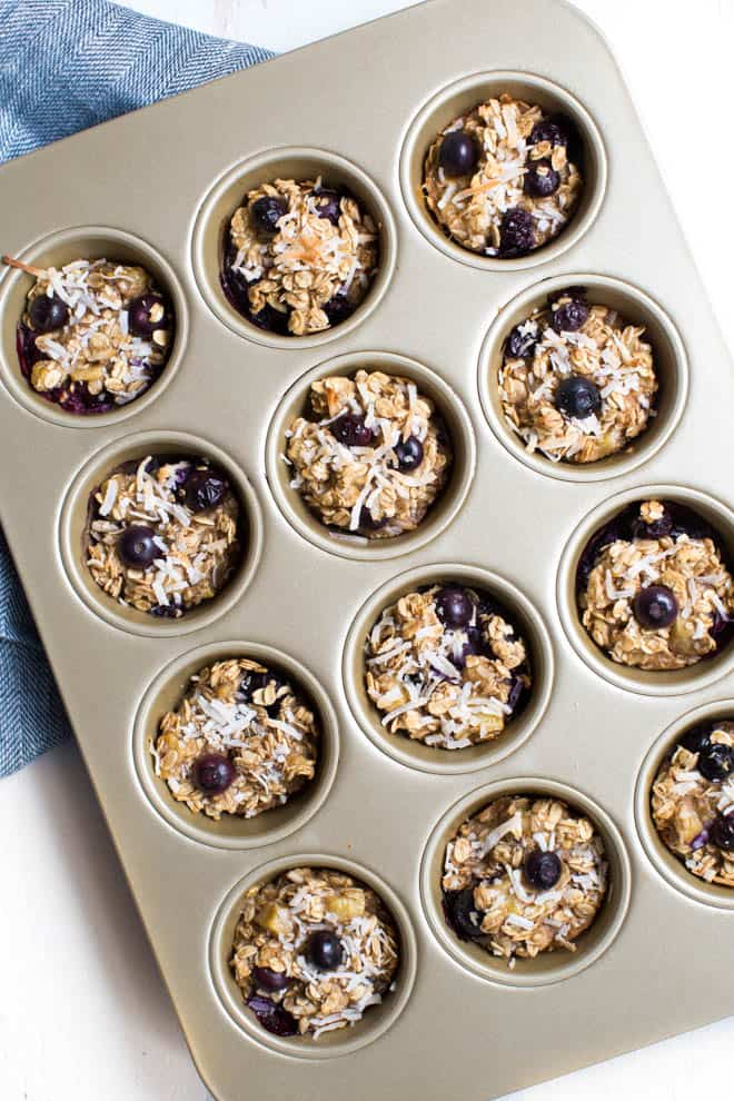 banana baked oatmeal cups with blueberries in a muffin tin