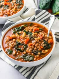 a bowl of lentil and kale sitting sitting on a tabletop