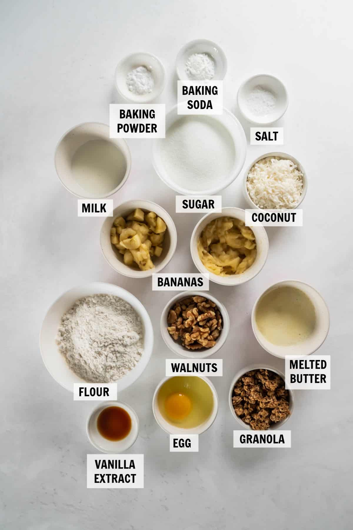 all of the ingredients for banana coconut muffins in bowls on a white countertop